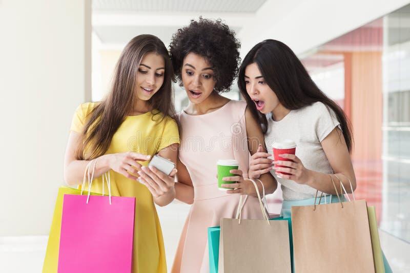 Mulheres emocionais que usam o smartphone ao comprar na alameda fotografia de stock royalty free