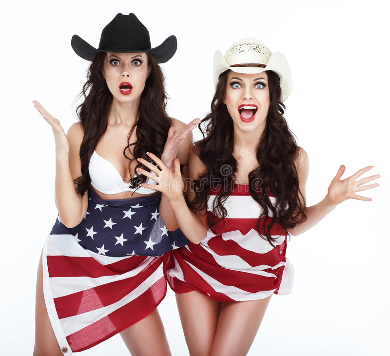Mulheres engraçadas nos chapéus envolvidos na bandeira dos EUA fotos de stock