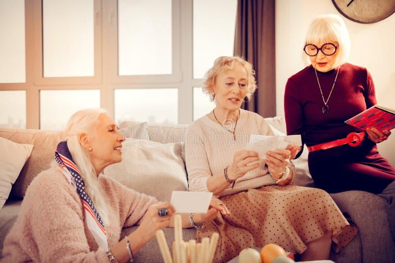 Mulheres envelhecidas agradáveis alegres que recordam sua juventude imagens de stock
