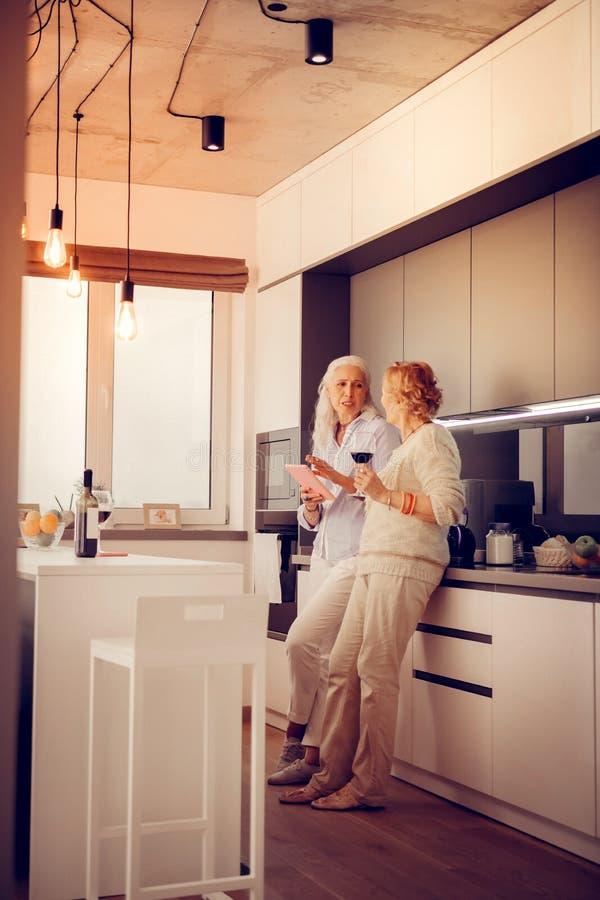 Mulheres envelhecidas agradáveis que estão na cozinha imagem de stock