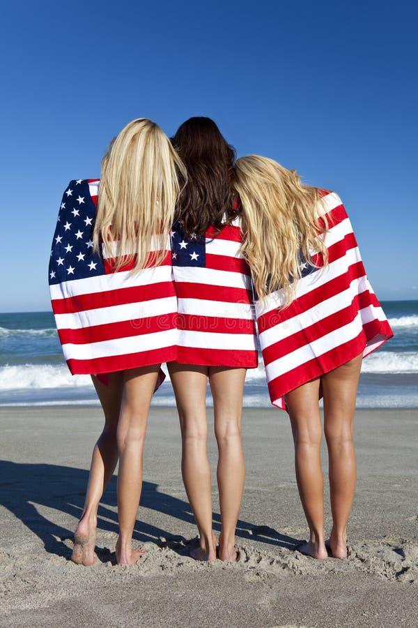 Mulheres envolvidas em bandeiras americanas em uma praia imagem de stock