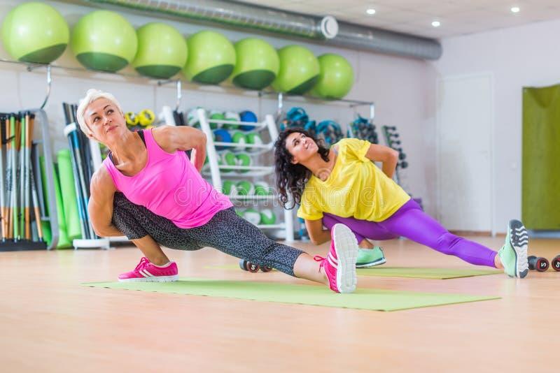 Mulheres fêmeas musculares da aptidão que fazem esticando o exercício dentro no clube desportivo imagem de stock