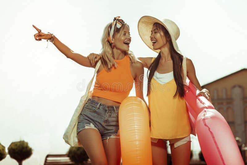 Mulheres felizes alegres brilhantes bonitas que guardam anéis da nadada nas mãos imagem de stock