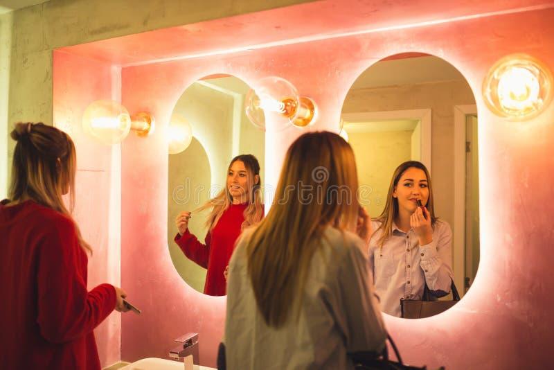 Mulheres felizes atrativas que aplicam a composição no banheiro de um restaurante fotos de stock royalty free