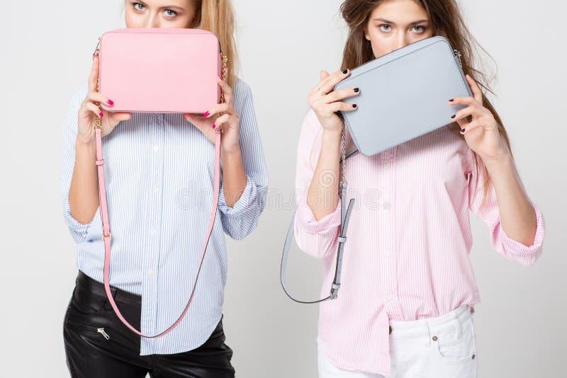 Mulheres felizes das amigas nas camisas com bolsas à moda Imagem da mola da forma de duas irmãs Rosa pastel e azul fotos de stock