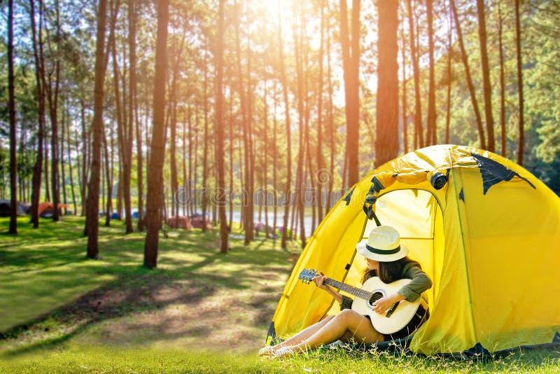 Mulheres felizes do viajante em férias que acampam com as barracas que jogam a guitarra na floresta perto do rio fotografia de stock royalty free