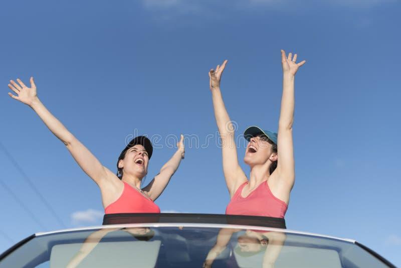 Mulheres felizes no telhado do carro do suv foto de stock royalty free