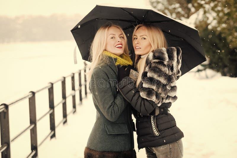 Mulheres felizes que sorriem sob o guarda-chuva no dia de inverno fotografia de stock