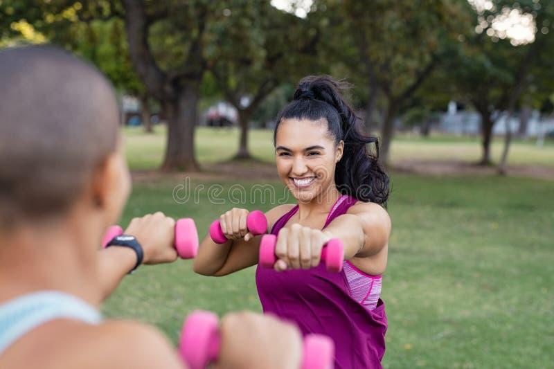 Mulheres felizes que treinam com pesos imagens de stock