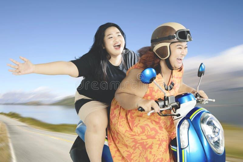 Mulheres gordas que apreciam suas férias com um 'trotinette' imagens de stock royalty free