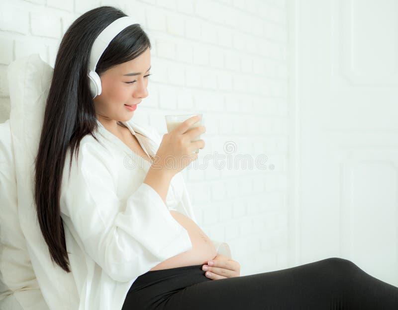 Mulheres grávidas lindas ouvem música dos fones de ouvido e bebem leite de soja. imagens de stock royalty free