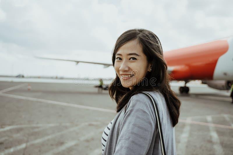 Mulheres gravidas asiáticas que puxam malas de viagem ao andar na pista de decolagem imagem de stock royalty free