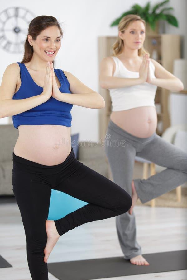 Mulheres gravidas durante a ioga imagens de stock