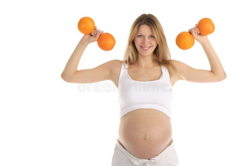 Mulheres gravidas envolvidas em laranjas da aptidão fotos de stock royalty free