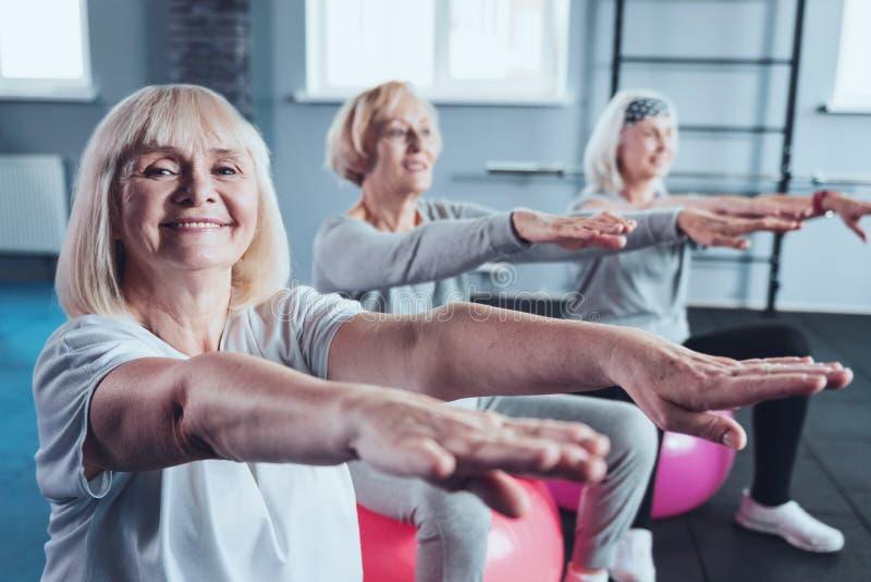 Mulheres idosas alegres que esticam as mãos no clube de aptidão imagens de stock royalty free