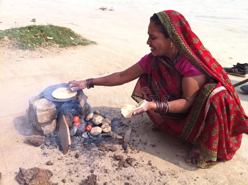Mulheres indianas que cozinham sobre o fogo de madeira imagens de stock royalty free