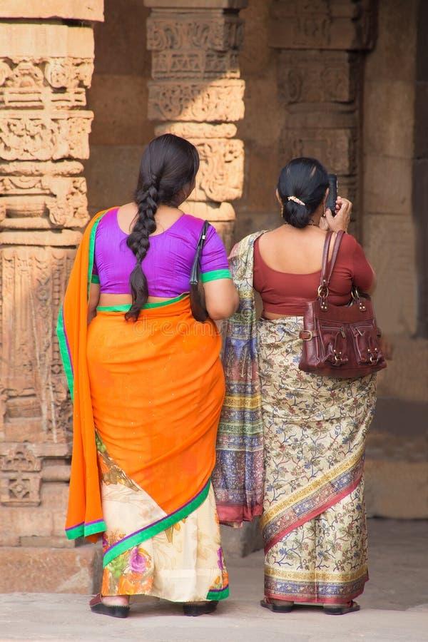 Mulheres indianas que estão no pátio da mesquita do Quwwat-Ul-Islã, Qu imagem de stock royalty free
