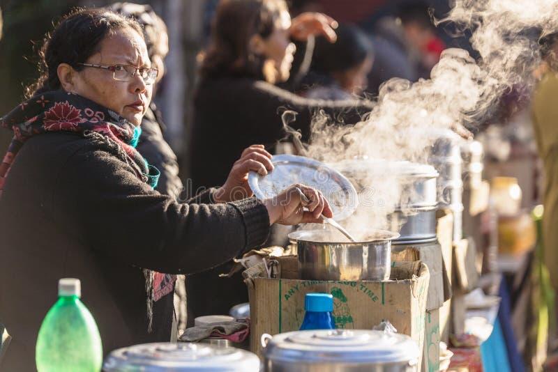Mulheres indianas que vendem o chá com vapor da bacia de aço inoxidável no mercado perto de Tiger Hill no inverno em Darjeeling,  imagens de stock