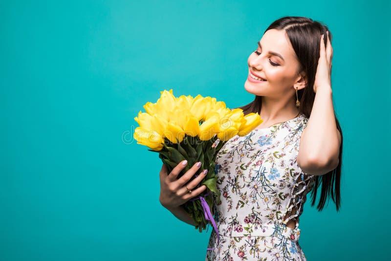 Mulheres internacionais dia, março oito Retrato bonito da mulher bonita com as tulipas amarelas no vestido elegante no fundo azul fotografia de stock royalty free