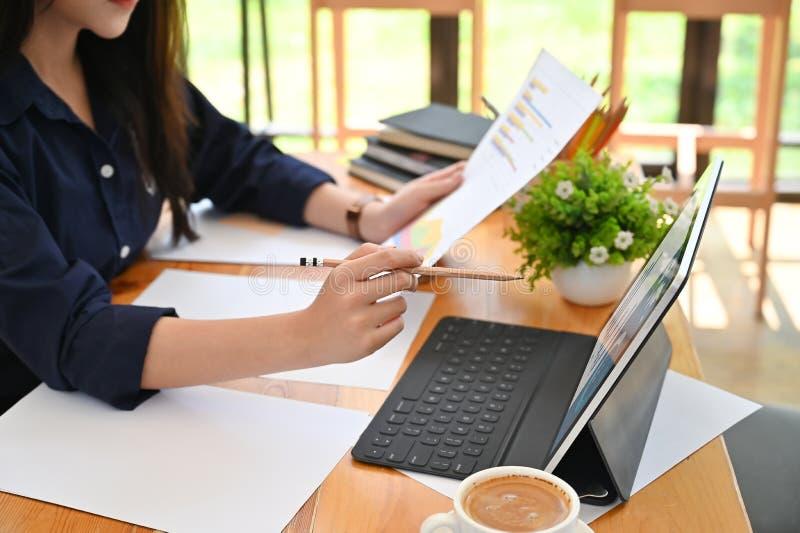 Mulheres jovens que usam um laptop e trabalham com papel em cooperação fotografia de stock