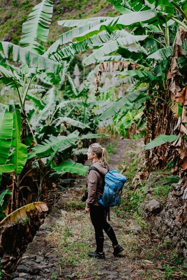 Mulheres louras de Yong com câmera e a trouxa azul que andam através da plantação de banana na rota trekking ao vale de Paul imagens de stock royalty free