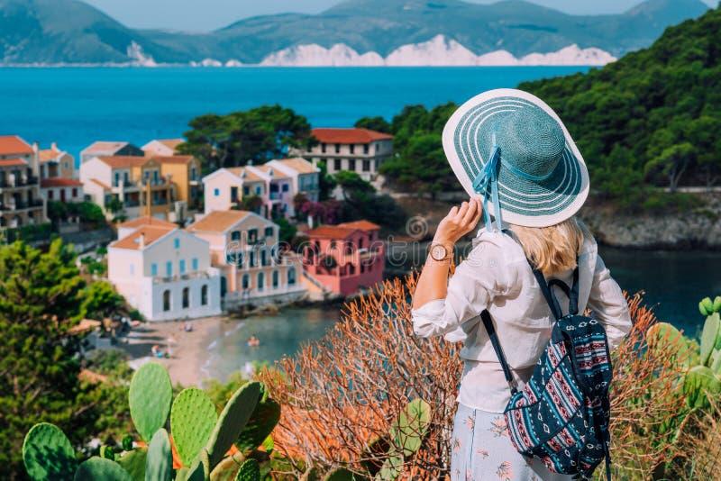 Mulheres louras do turista com o chap?u do sol na vila pequena colorida bonito de Assos Kefalonia, Greece imagem de stock royalty free