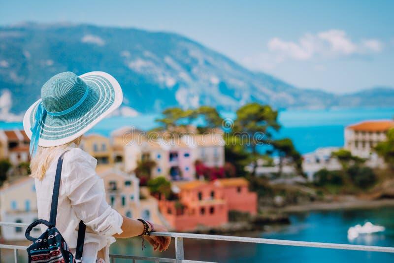 Mulheres louras do turista com o chap?u do sol na vila pequena colorida bonito de Assos Kefalonia, Greece imagens de stock