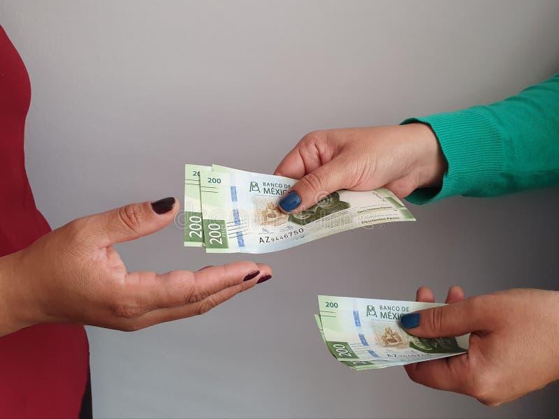 mulheres mãos pagando e recebendo dinheiro mexicano fotografia de stock royalty free