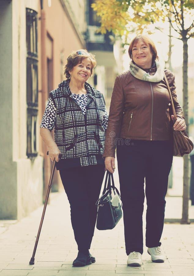 Mulheres maduras contentes felizes que andam na cidade imagens de stock royalty free