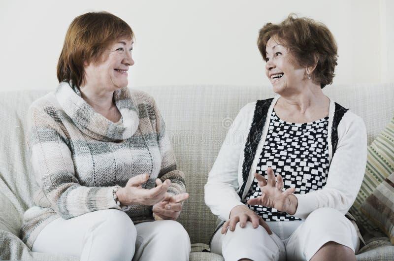 Mulheres maduras contentes felizes que sentam-se no sofá imagens de stock