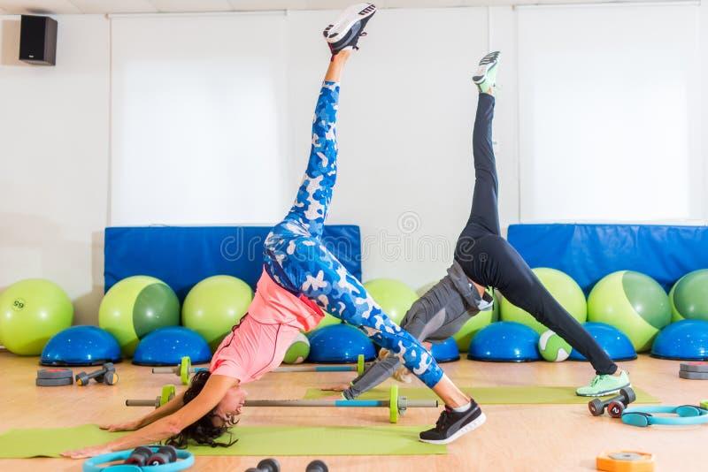 Mulheres magros do ajuste que praticam a ioga dentro no estúdio da aptidão Duas fêmeas atléticas que estão em descendente Um-equi fotografia de stock