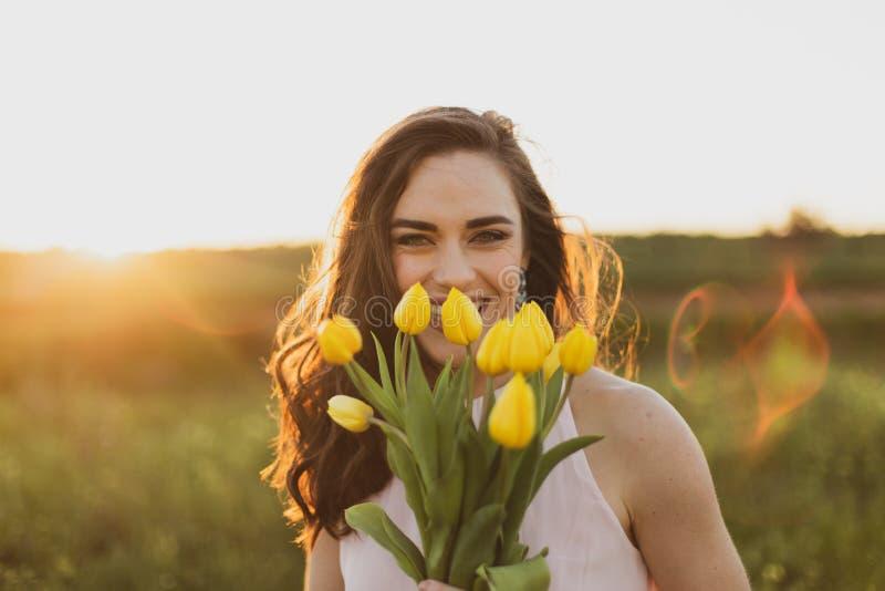 Mulheres morenos felizes bonitas que guardam flores no por do sol fotografia de stock royalty free
