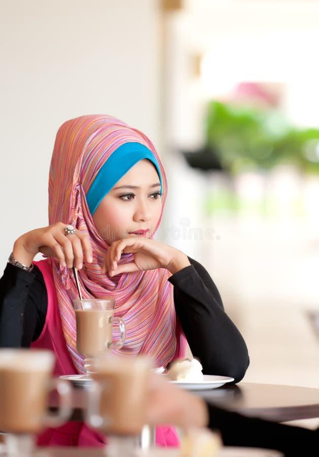 Mulheres muçulmanas novas na mesa de centro imagens de stock