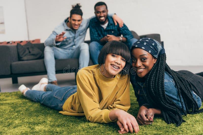 mulheres multi-étnicos de sorriso novas que colocam no tapete e em dois amigos masculinos imagem de stock