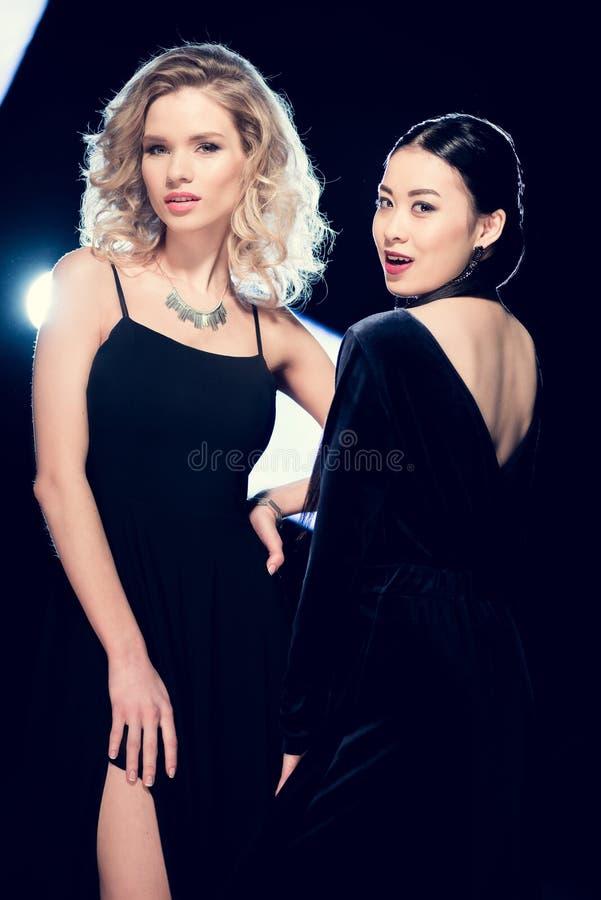 Mulheres multiculturais do encanto sedutor que levantam em vestidos de noite pretos e que olham a câmera no partido imagem de stock royalty free