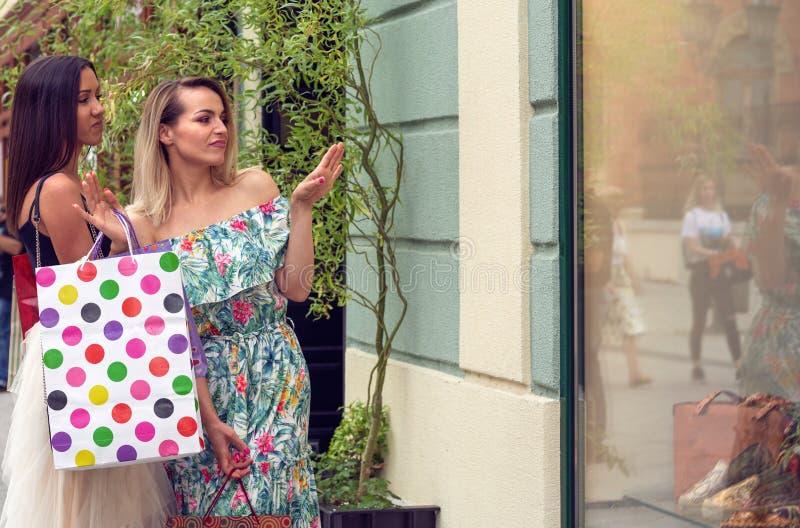Mulheres na compra que olha a janela da loja na cidade fotografia de stock royalty free