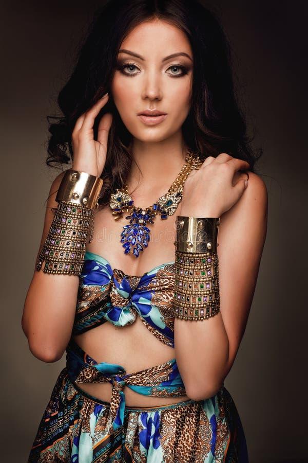 Mulheres na roupa asteca no fundo escuro com acessórios do ouro foto de stock