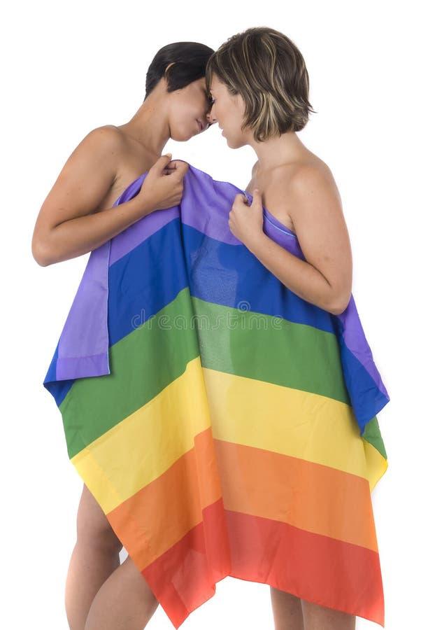 Mulheres no amor com a bandeira do arco-íris da lésbica fotografia de stock royalty free