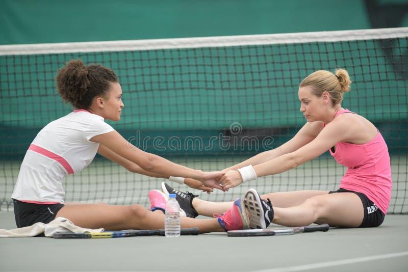 Mulheres no campo de tênis que estica junto imagens de stock royalty free
