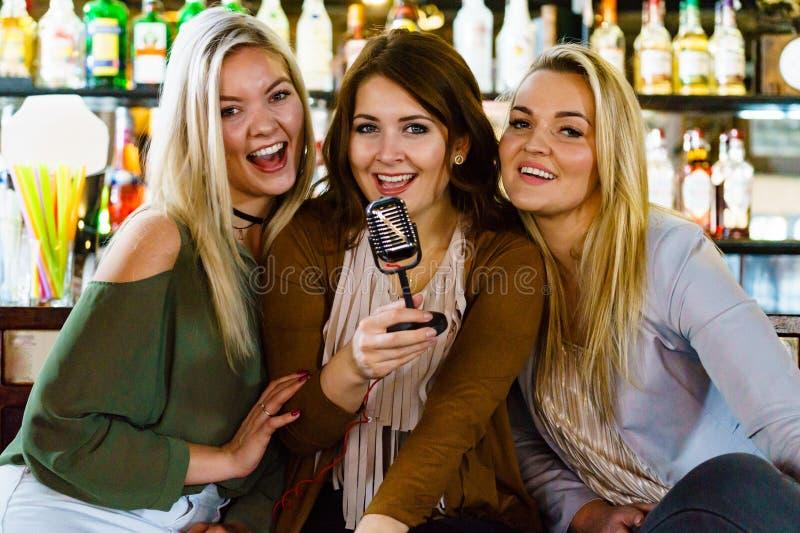 Mulheres no karaoke do canto da barra foto de stock royalty free