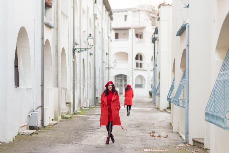 Mulheres no vermelho que andam abaixo da rua foto de stock royalty free