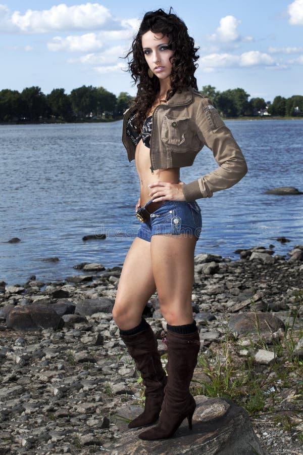 Mulheres novas bonitas da forma pelo lago foto de stock