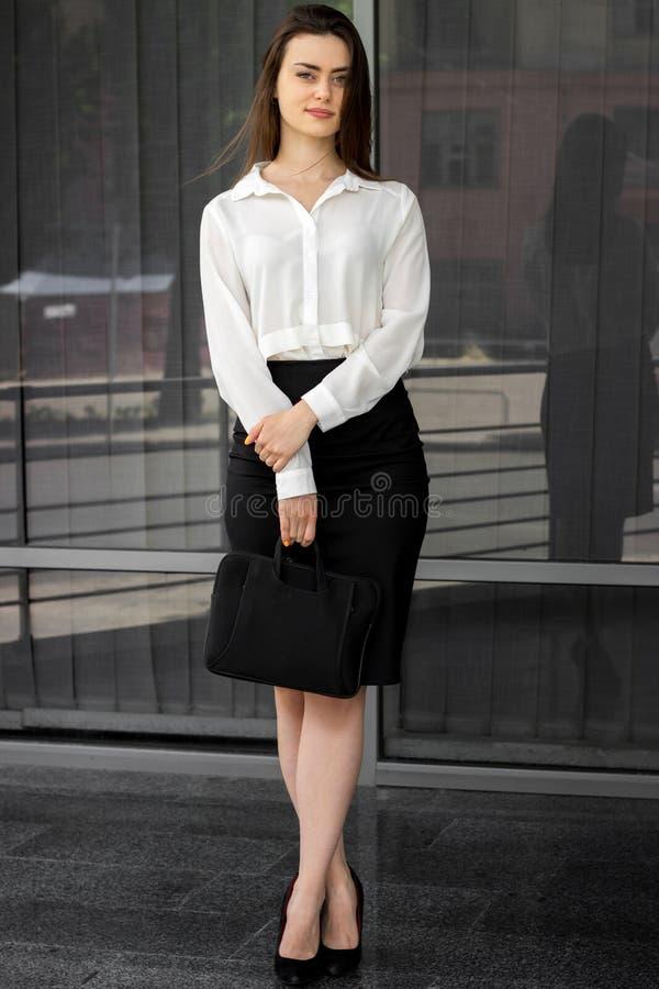 Mulheres novas bonitas do escritório em suportes de uma camisa branca e da saia na rua fotografia de stock