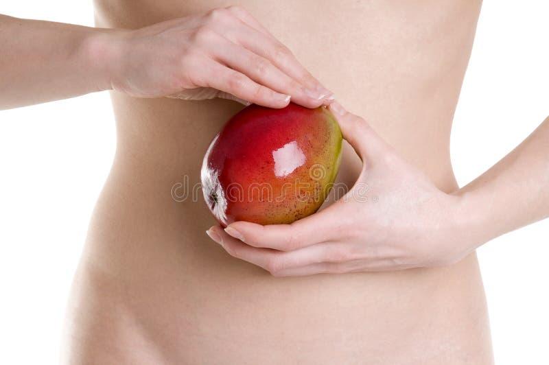Mulheres novas com fruta da manga nos termas foto de stock