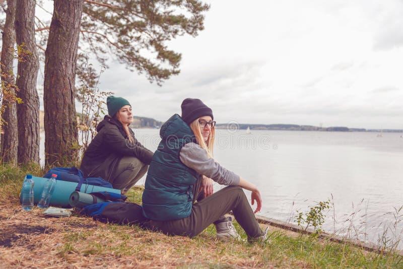 Mulheres novas do viajante que descansam durante a viagem perto do lago foto de stock
