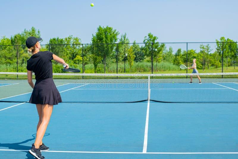 Mulheres novas dos esportes que jogam o tênis no campo de tênis azul fotos de stock