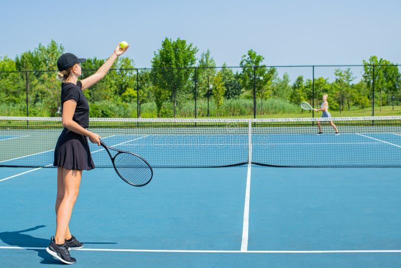 Mulheres novas dos esportes que jogam o tênis no campo de tênis azul imagens de stock royalty free