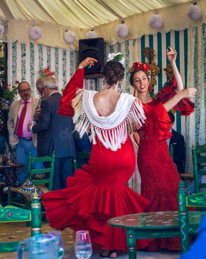 Mulheres novas e bonitas que vestem vestidos do flamenco e que dançam 'Sevillanas em April Fair, Sevilha Feria de Sevilla justa imagem de stock royalty free