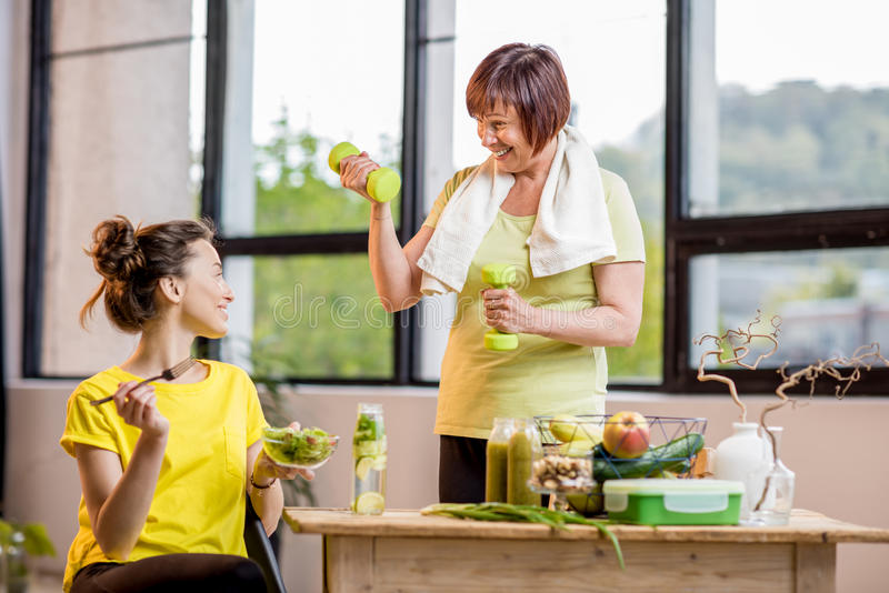 Mulheres novas e mais idosas com alimento saudável dentro fotografia de stock