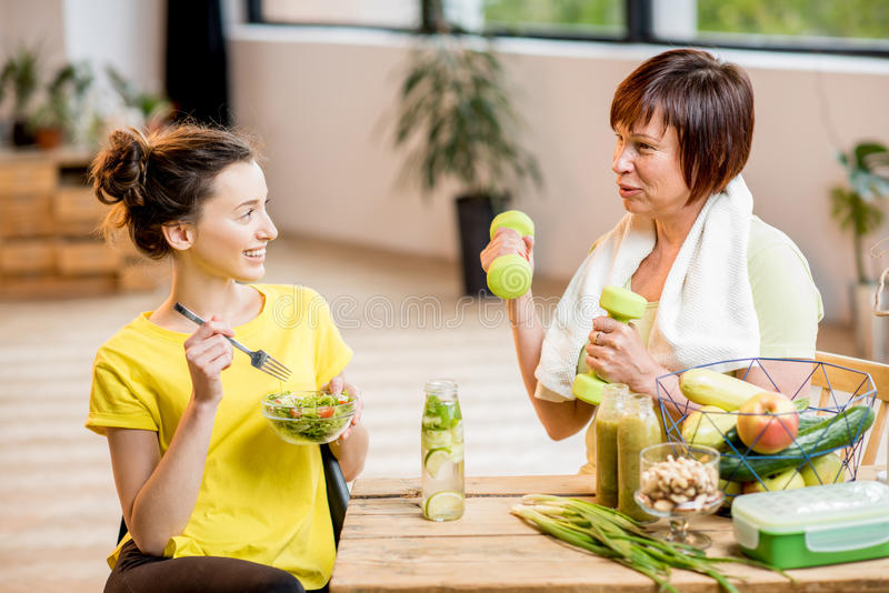Mulheres novas e mais idosas com alimento saudável dentro foto de stock